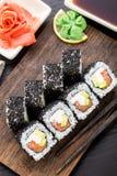 Rollo de sushi de color salmón cubierto con sésamo Foto de archivo libre de regalías