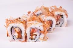 Rollo de sushi de color salmón en escamas del atún Fotos de archivo