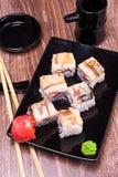 Rollo de sushi de la anguila con el jengibre, la salsa de soja, la toalla y los palillos Foto de archivo