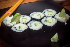 Rollo de sushi de Vegeterian con el aguacate en la placa negra imagenes de archivo