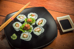 Rollo de sushi del pollo con lechuga en la placa negra fotografía de archivo