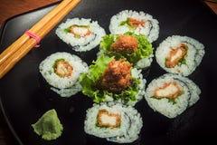 Rollo de sushi del pollo con lechuga en la placa negra foto de archivo libre de regalías