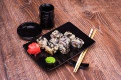 Rollo de sushi del Tempura con el jengibre, la salsa de soja y los palillos Imagenes de archivo