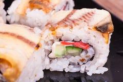Rollo de sushi del unagi de la anguila en fondo de madera Imagenes de archivo