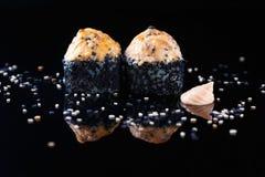 Rollo de sushi delicioso con los pescados y el sésamo en un fondo negro con el menú de la reflexión y el concepto del restaurante imágenes de archivo libres de regalías