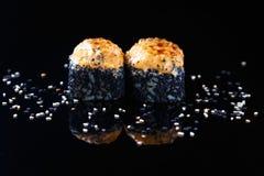Rollo de sushi delicioso con los pescados y el sésamo en un fondo negro con el menú de la reflexión y el concepto del restaurante fotos de archivo