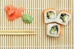 Rollo de sushi en la estera de bambú Imagenes de archivo