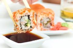 Rollo de sushi en palillos Imagenes de archivo