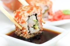 Rollo de sushi en palillos Imagen de archivo libre de regalías