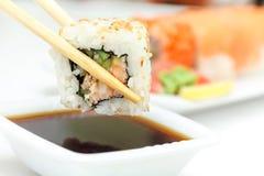 Rollo de sushi en palillos Fotos de archivo libres de regalías
