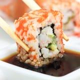 Rollo de sushi en palillos Fotos de archivo