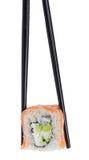 Rollo de sushi en palillos en blanco Imágenes de archivo libres de regalías