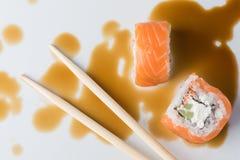 Rollo de sushi en palillos en salsa de soja, Imagenes de archivo