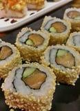 Rollo de sushi japonés delicioso de la comida Maki de salmones rojos y del aguacate verde con sésamo en la placa negra Imagen de archivo libre de regalías