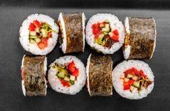 Rollo de sushi - Maki Sushi con pimienta, el pepino, el tomate y la col en la placa negra imágenes de archivo libres de regalías