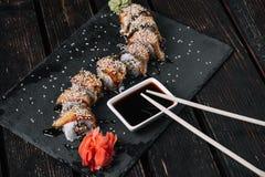 Rollo de sushi de oro del dragón con el atún, anguila, pepino, semillas de sésamo foto de archivo