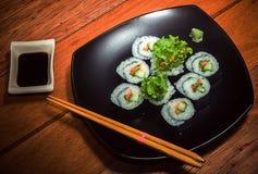 Rollo de sushi vegetariano en la placa negra fotografía de archivo