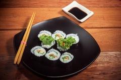 Rollo de sushi vegetariano en la placa negra imagen de archivo