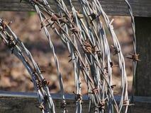 Rollo del alambre de púas con la cerca de madera Background Fotos de archivo libres de regalías