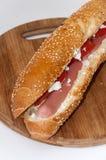 Rollo del bocadillo con queso de la vaca del tomate del perrito caliente Foto de archivo libre de regalías