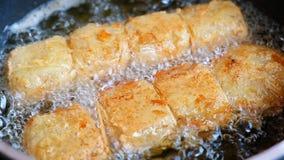 Rollo del cerdo que fríe en cacerola en la cocina es comida malsana que contiene muchas de colesterol y de grasa almacen de metraje de vídeo
