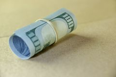 Rollo del dinero con el billete de dólar del nuevo ciento de los E.E.U.U. Imágenes de archivo libres de regalías
