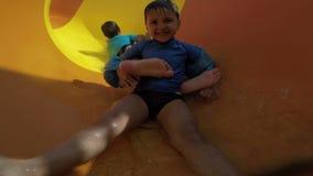 Rollo divertido del niño con los toboganes acuáticos amarillos almacen de video