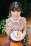 Rollo feliz adolescente joven de la torta del postre de la consumición del inconformista de la muchacha asiática Foto de archivo