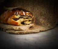Rollo fresco de la semilla de amapola en servilleta de lino natural en fondo de madera rústico fotografía de archivo