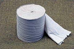 Rollo gris del papel higiénico en el paño verde foto de archivo