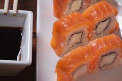 Rollo, salsa y palillos de sushi de Philadelphia en la encimera de madera, primer imagenes de archivo