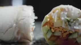 Rollo vegetariano con la zanahoria, el pepino, la pimienta y la subida en dos porciones El cocinero prepara la comida para servir almacen de metraje de vídeo