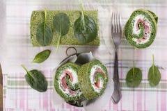 Rollo verde de la espinaca con queso suave y salmones imagen de archivo