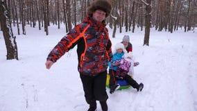 Rollos bebé y mamá del papá en el platillo de la nieve que corre en bosque nevoso y risa del invierno El hombre y la mujer con su almacen de metraje de vídeo