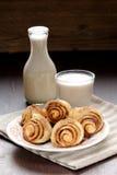 Rollos de canela con el vidrio y la botella de leche Fotografía de archivo libre de regalías
