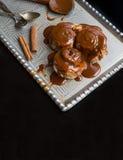 Rollos de canela con los palillos calientes del desmoche y de canela del caramelo encendido Fotografía de archivo
