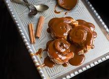 Rollos de canela con los palillos calientes del desmoche y de canela del caramelo encendido Imagen de archivo libre de regalías
