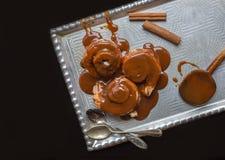 Rollos de canela con los palillos calientes del desmoche y de canela del caramelo encendido Fotografía de archivo libre de regalías