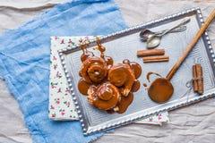 Rollos de canela con los palillos calientes del desmoche y de canela del caramelo encendido Foto de archivo