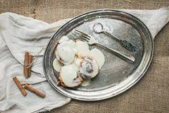 Rollos de canela con los palillos de la formación de hielo y de canela del queso cremoso en a Imágenes de archivo libres de regalías