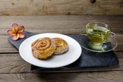 Rollos de canela con té del crisantemo en el fondo de madera Foto de archivo libre de regalías