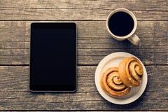 Rollos de canela, taza de café y tableta del ordenador Imagenes de archivo
