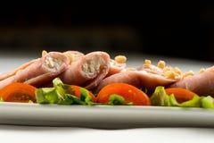 Rollos de carne con el jamón, el queso y verdes, en el fondo blanco foto de archivo