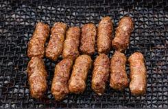 Rollos de carne rumanos asados a la parrilla en la rejilla de la barbacoa - mititei, mici Imagen de archivo libre de regalías