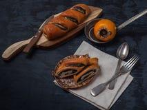 Rollos de la amapola en las placas decorativas, caqui maduro, cubiertos, platos, en un fondo oscuro Primer foto de archivo