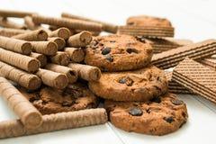 Rollos de la galleta del chocolate, galletas y galleta cl?sica en fondo blanco de madera fotografía de archivo libre de regalías
