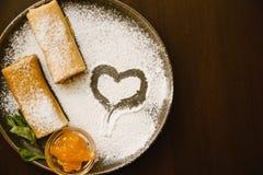 Rollos de las crepes en una placa oscura con el azúcar en polvo, el atasco y la menta Postre delicioso foto de archivo libre de regalías
