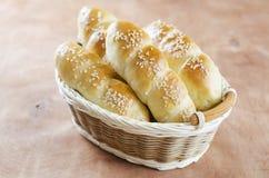 Rollos de pan hecho en casa frescos con la semilla del sesam en cesta en t de madera fotos de archivo