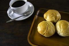 Rollos de pan y un café sólo en un plato Fotos de archivo