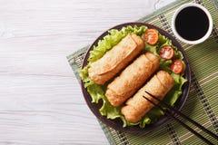 Rollos de primavera fritos en una placa con la ensalada, visión superior horizontal Fotos de archivo